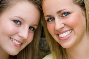 Two gorgeous young blond women shot in close up.